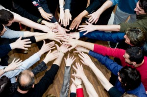 Close-up of friends joining hands in a circle