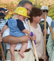 man with daughter at community groundbreaking event