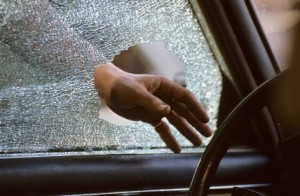 hand reaching through broken glass into car window