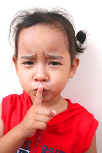 girl holding her finger up to her mouth to stop gossip