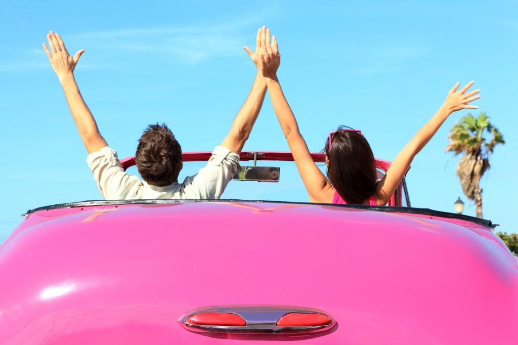 Man and woman in pink convertible cheering over guest bloggers