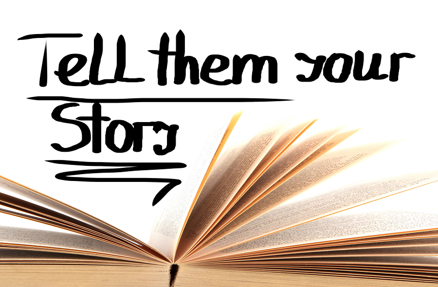 "Open book with the words ""Tell Them Your Story"" above"